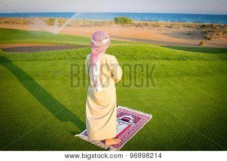 Muslim Arabic boy praying on green meadow