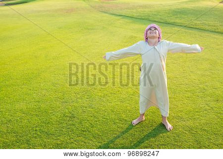 Happy Arabic cute boy on green meadow