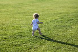 foto of runaway  - Happy runaway curly barefoot little boy on summer green grass meadow sunny day outdoor horizontal photo - JPG