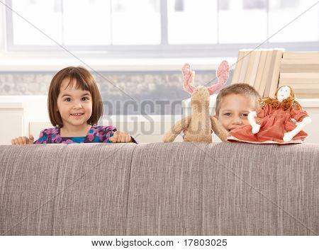 Kids standing behind sofa with toys, looking at camera, smiling.?