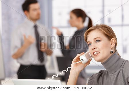 Young businesswoman talking on phone in office, colleagues chatting in background.?