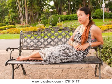 Distracted Asian Women Lay Down On Bench In Park