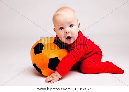 Surprised boy with black and orange soccer ball