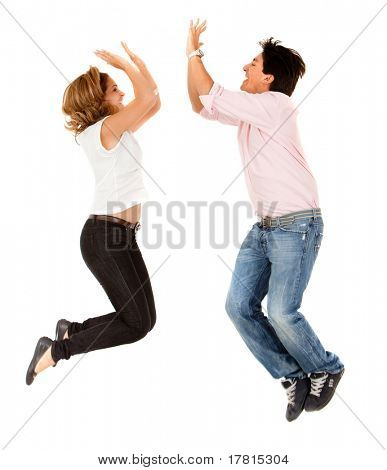 Enthusiastic couple jumping and making a high-five isolated