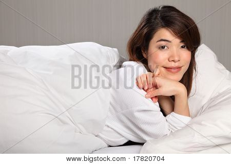 Young woman relaxing in bed smiling
