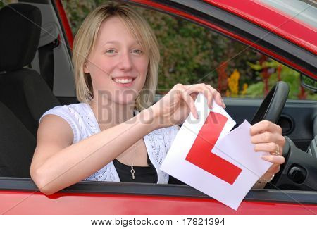 Young woman ripping up learner driver plates