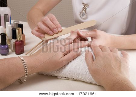 Manicurist filing nails of customer in nail salon