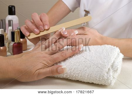 Manicurist filing client's nails