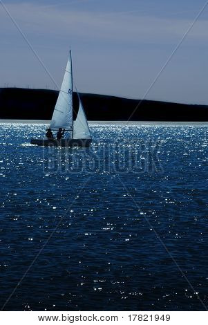 Small sailing boat on moonlit estuary