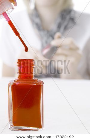 Red nail polish with manicurist in background