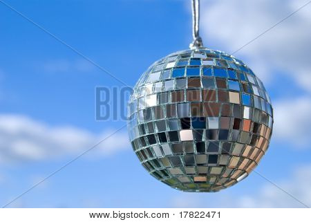 Disco glitter ball against a blue sky