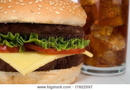 Close up of a double cheeseburger with cola drink in background