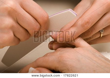 Manicurist filing down the acrylic after fixing on a false nail