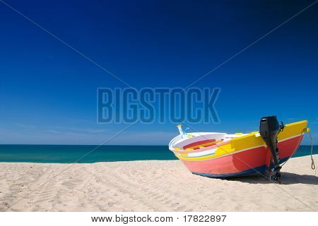 Bright painted small fishing boat in the beach