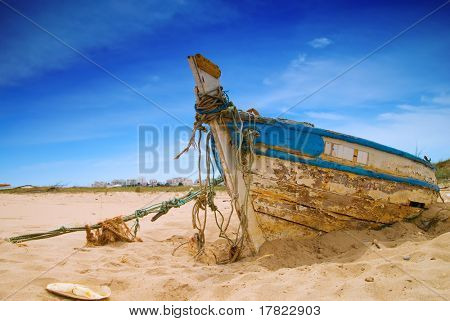 Dilapidated fishing boat in the sand
