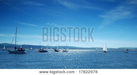 Small recreational sailing boats backlit with cool blue tone on an estuary in Wales, UK