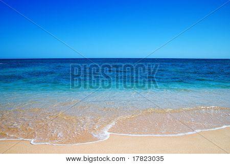 Hermosa agua clara mediterránea traslapar en la orilla
