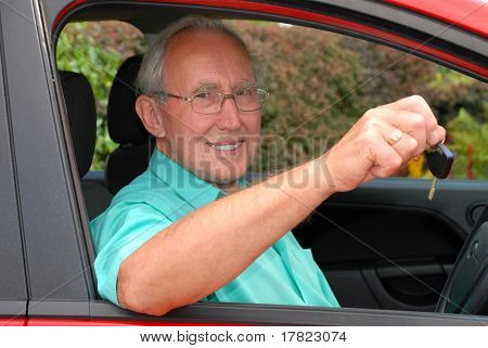 Never too late to learn - a senior man passes his driving test and gets the keys to his car.