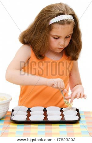 Young girl putting out the cake mixture into paper cases, isolated on white background