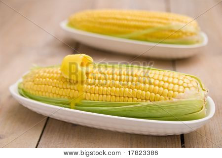 Corn on the cob sweetcorn in dishes on a rustic table