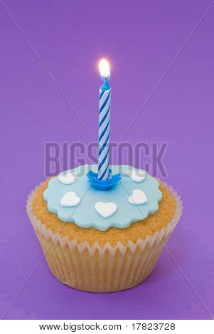 Single cupcake with blue lit candle and icing with white hearts on purple background