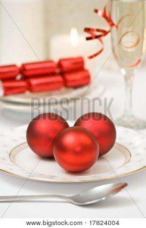 Christmas table setting with champagne and red baubles and crackers