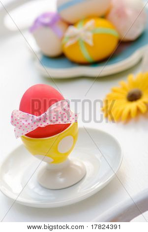 Decorated Easter eggs in eggcup with spotty bow