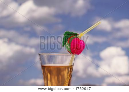 Cocktail With Drinking Straw Against Cloudy Sky