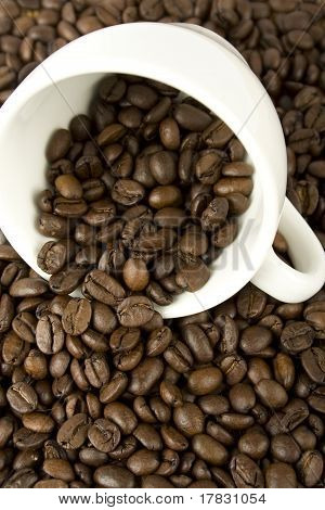 Coffee beans are scattered from a white cup
