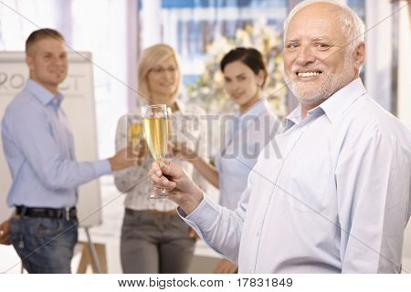 Senior businessman raising champagne glass to toast, smiling at camera, team celebrating in background.?
