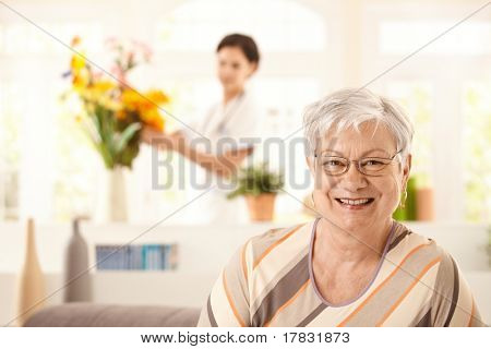 Portrait of happy elderly woman sitting on sofa at home, nurse arranging flowers in background.?