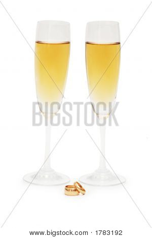 Two Wine Glasses And Wedding Rings Isolated