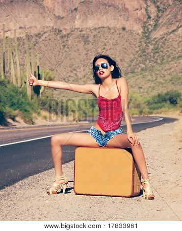 Beautiful young lady with case hitching a ride on a lonely hot desert road