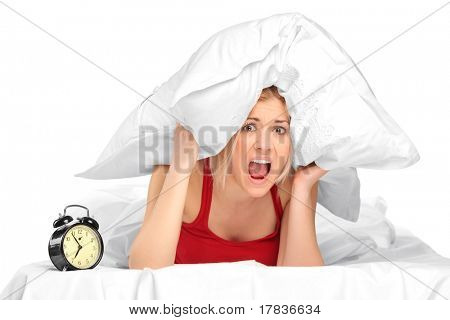 Woman screaming and covering her ears with pillow because of noise