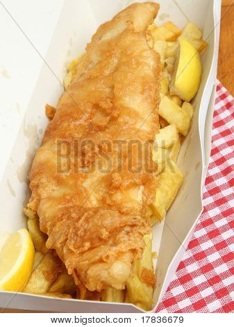Fried cod fish with chips in takeaway carton.