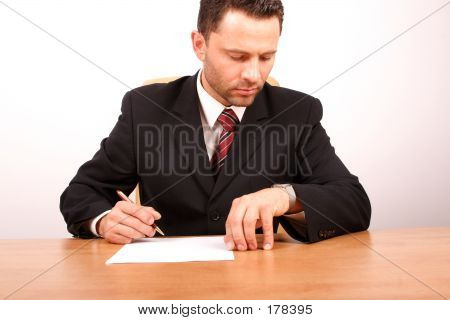 Businessman Signing The Paper Is Looking At His Watch