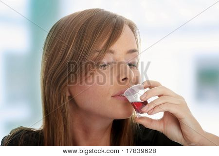 Young woman taking pills and syrup, isolated on white