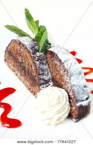 Chocolate Cake With A Spherule Of Ice Cream And Strawberry Sauce