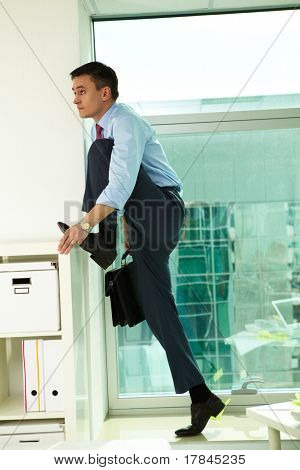 Portrait of handsome man standing by the window in office with one leg raised