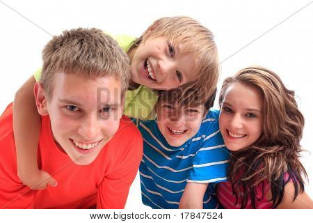 Four smiling siblings, three boys and one girl,  isolated against a white background.