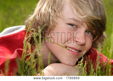 Teenage Boy Laying In A Field Of Grasses