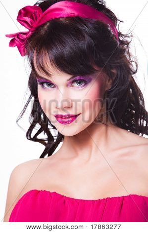 Portrait of beautiful girl with dark hair wearing pink on white background