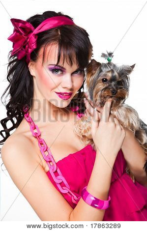 beautiful girl with dark hair wearing pink holding small dog on white