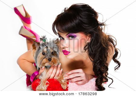 beautiful girl with darkhairwearing pinkholding small dog on white