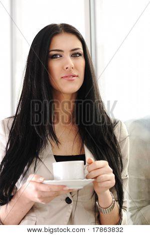 junge hübsche geschäftsfrau Kaffeetrinken in Büro neben der Glasfenster