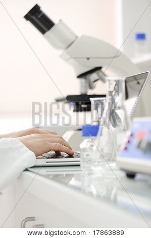 Working in lab with microscope and writing results on laptop, closeup