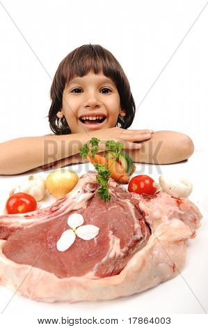 Cute positive boy and raw meat and vegetables in plate reading for cooking