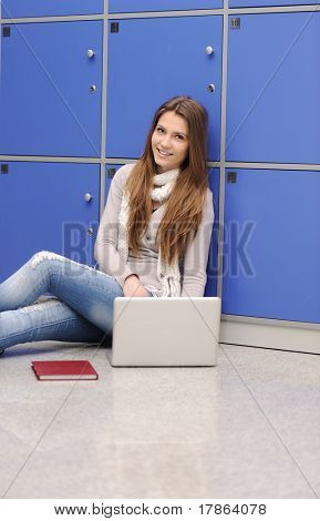 Beautiful female student sitting on ground at college with laptop