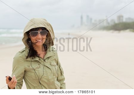 Young Girl Enjoys To Listen Music On The Beach