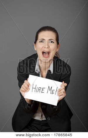 "Business woman holding a card board with the text message ""Hire me"" and beging for a job."